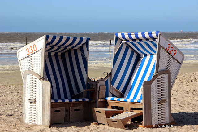 Two blue and white striped beach chairs marked 330 and 329 on a white sand beach by the sea under a bright blue sky.