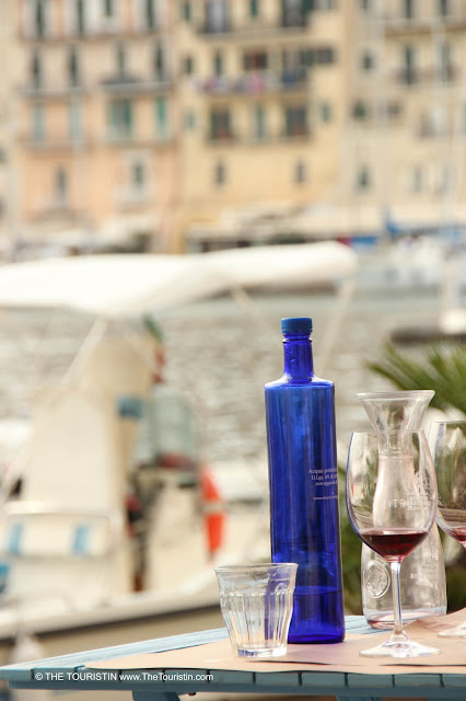 An empty water glass next to the rest of red wine in a glass and a blue water bottle with yachts and house facades in the background.
