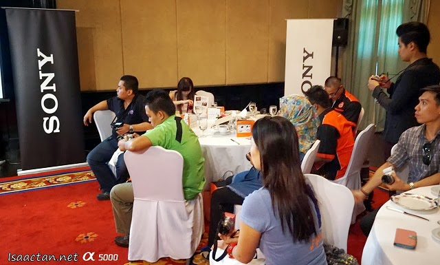 A candid shot of the bloggers at the gathering, each one concentrating on checking out Sony Alpha 5000's functions