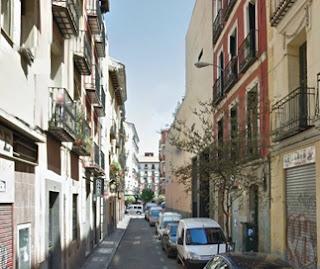 Estrecha calle, con edificios de tres alturas con balcones.