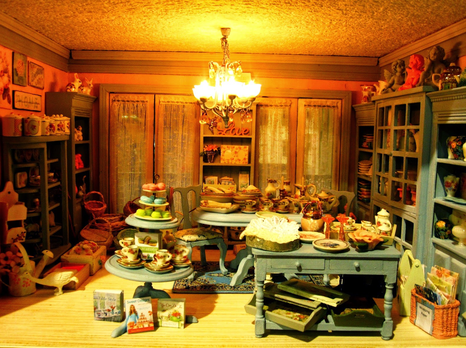 The first floor fo a modern miniature shabby chic shop, with blue cabinets displaying a range of dinnerware and decorative items.