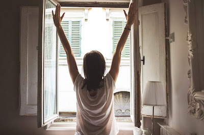 Woman's back to us with arms outstretched looking out of a window ready to face world.