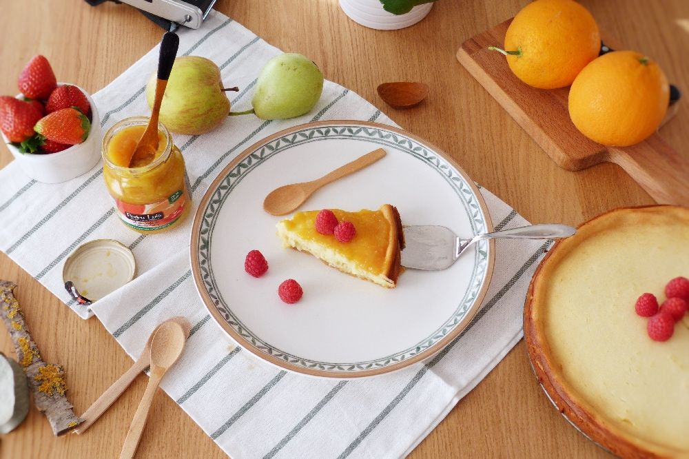 mesa puesta para la merienda, tarta de queso, mermelada de naranja, frutas, cucharas de madera