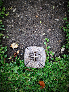 photographs of a cross on the ground in a cemetery on a rainy day by andreas warren matti