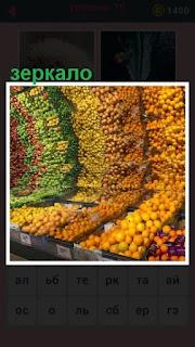 в магазине на зеркальном прилавке лежат разные фрукты