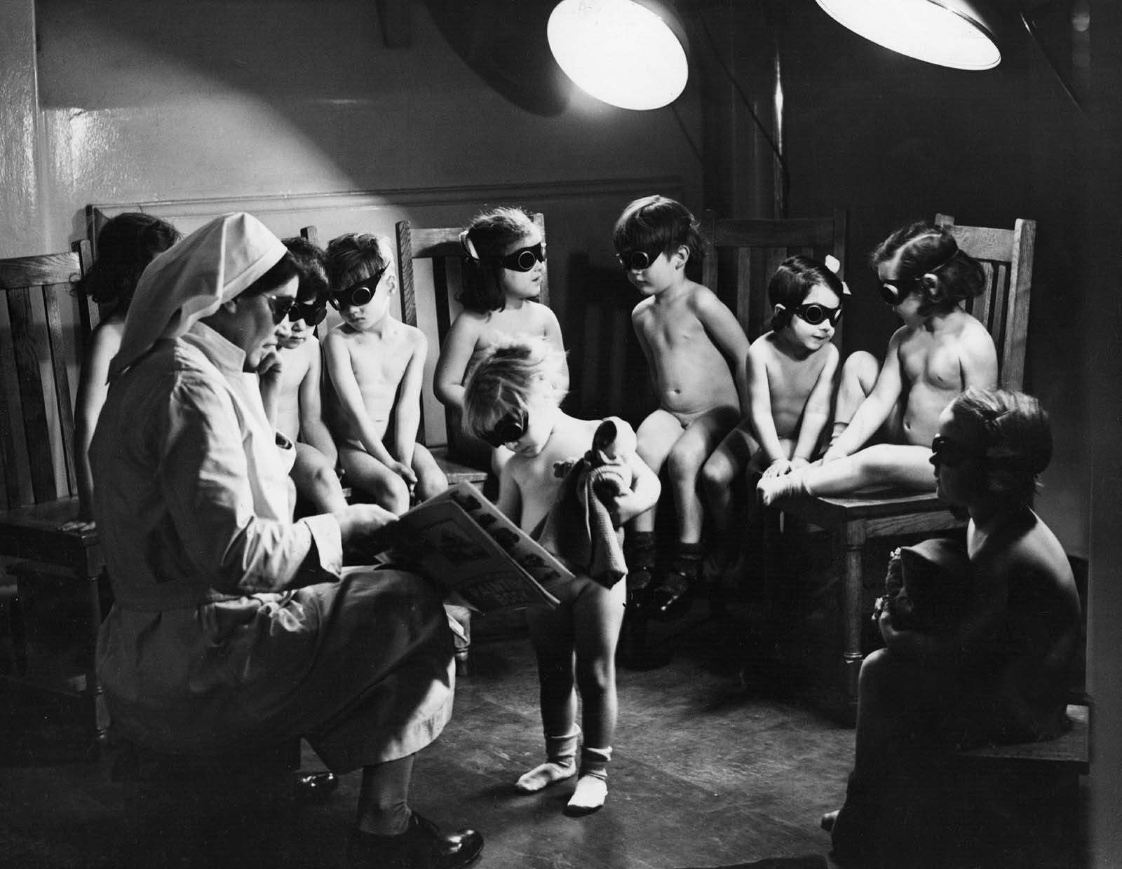 A nurse watching over children in Bermondsey, London, sitting under sun-ray lamps to help make up the deficiency in sunlight and the lack of certain items of food, such as fruit, during the winter months of the Second World War. 1942.