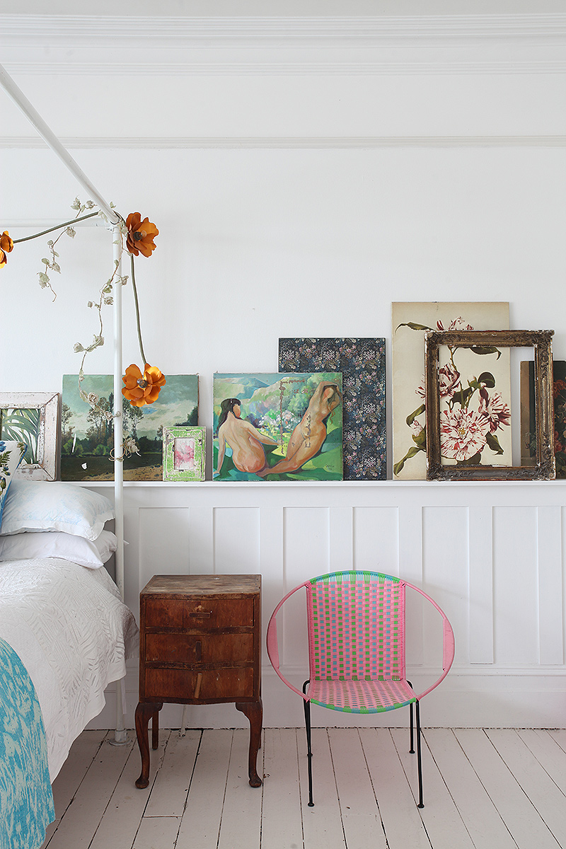 bohemian bedroom decor with paintings, white painted floors and rustic furniture