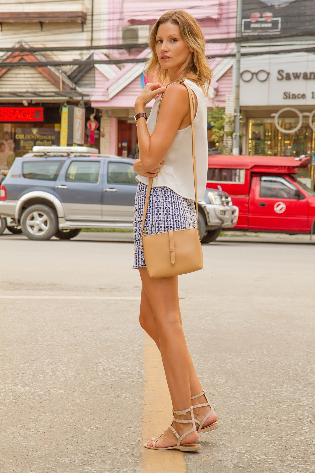 fashion and travel blogger, Alison Hutchinson, is wearing a blue mini skirt and white crop top in Chiang Mai, Thailand