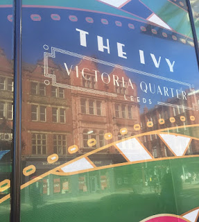 A bright blue billboard with the ivy in bold white font with Victoria Quarter and coming soon in smaller white font on a bright background