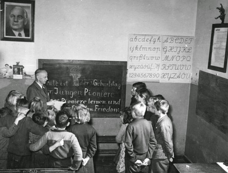 Black and white photo of an old classroom.  Source: http://upload.wikimedia.org/wikipedia/commons/7/7e/Bundesarchiv_Bild_183-13055-0008,_Hohendorf,_JP_mit_Dorflehrer.jpg
