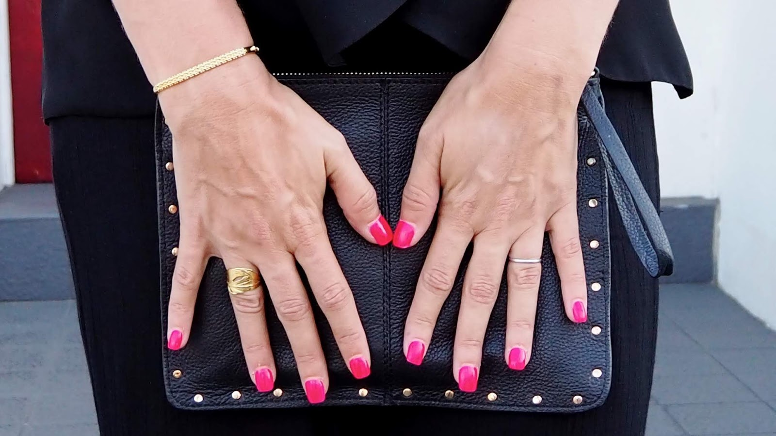 Gold bangle, gold leaf ring, hot pink nails, black leather clutch with gold studs