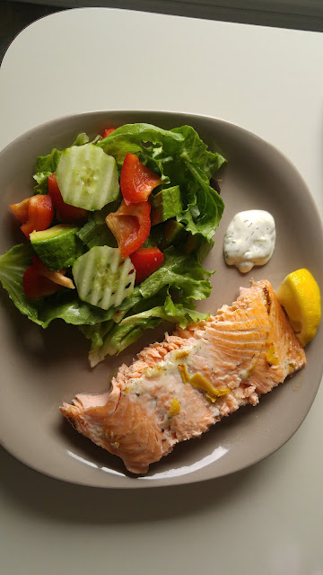 A plate of baked salmon covered with dill dip and lemon zest with salad on the side.