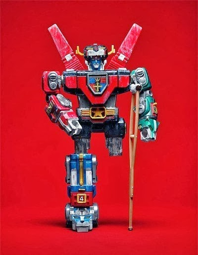"""Transformer"" style robot toy with leg missing and using a traditional wooden crutch"