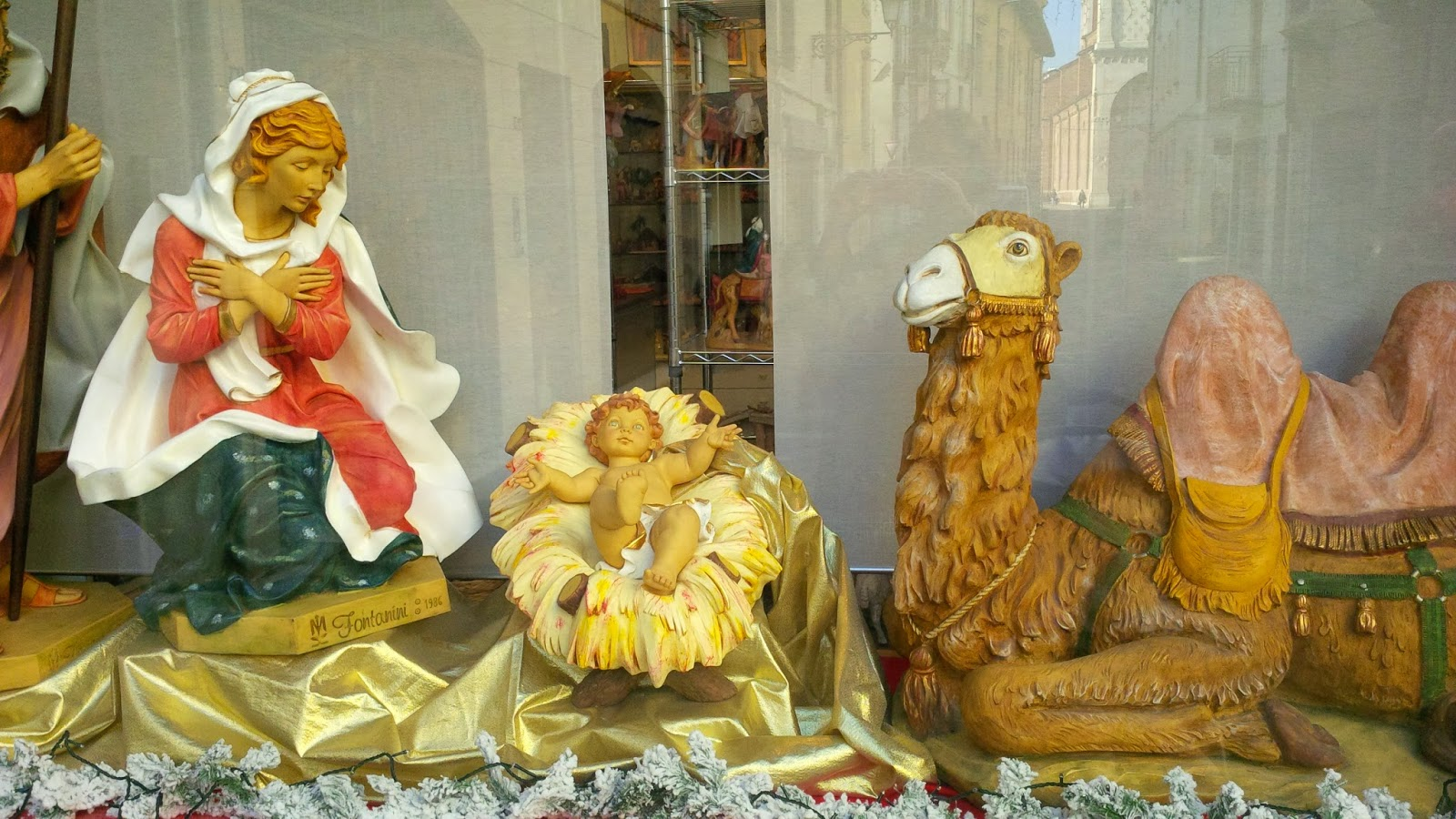A blue-eyed flame-haired baby Jesus in a Biblical window display in Vicenza