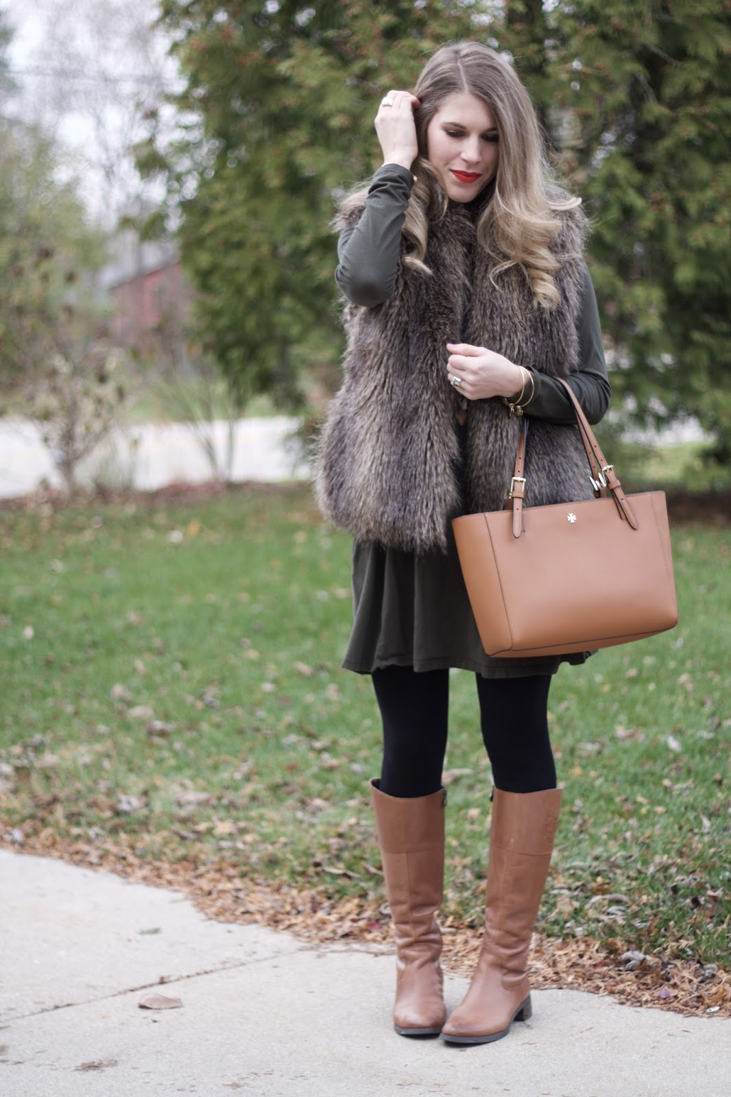 fur vest, olive green tunic dress, black leggings, cognac riding boots, Tory Burch tote, long gold necklace