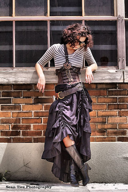 Tutorial on how to recreate this casual, chic, easy, sexy Steampunk outfit. Striped boatneck top, striped underbust corset, leather harness with LED light, cyclops monocle, black high low hem showgirl skirt, black leather boots, brown wide leather belt. Women's Steampunk clothing