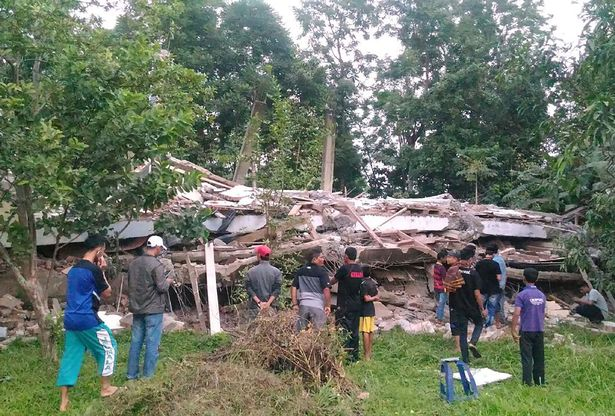 Residents-gather-around-a-collapsed-buil (1)