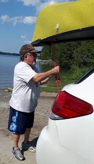 A guy tying a yellowcanoe onto the top of his car.