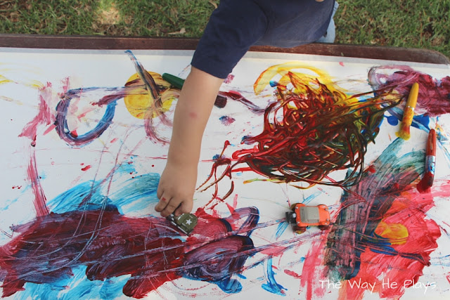 Toddler painting with a car