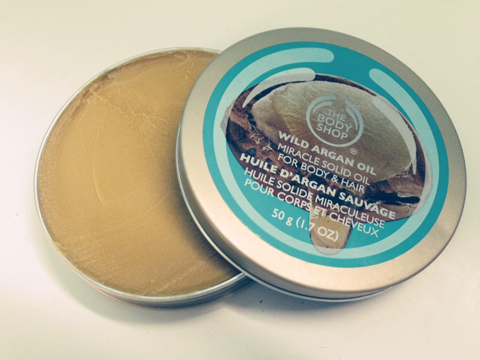 An open tin of Wild Argan Oil by the Body Shop showing the golden balm inside