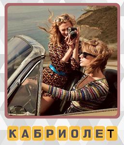 две девушки едут в кабриолете, одна из них фотографирует