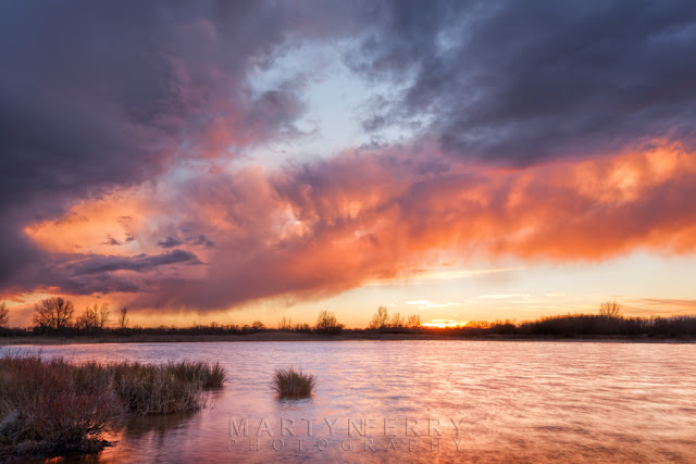 Vibrant clouds at sunset over one of the lakes at Ouse Fen Nature Reserve