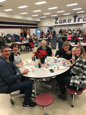 A family sitting around a table together in a cafeteria enjoying their santa breakfast