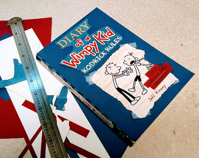 A book on a counter, 'Rodrick Rules' by Jeff Kinney, with a paper-collage front cover. Next to it are a pica pole and paper scraps in blue, white, and rust