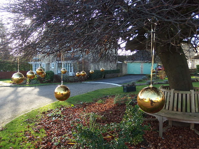 Front garden tree decorated with large baubles for Christmas