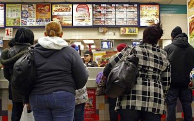 Personas aguardan en una fila de comida rápida.