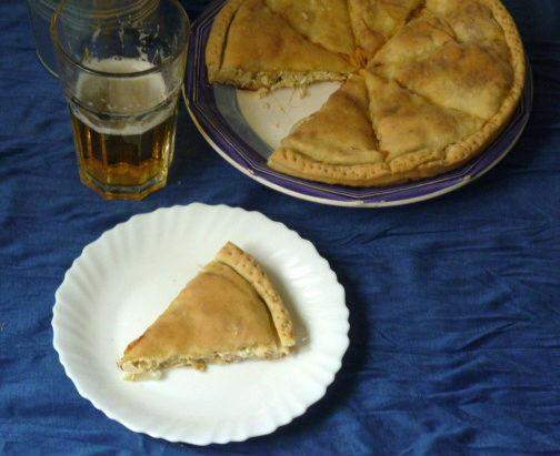 """Se andate a Folegandros e volete mangiare una pita, sappiate che dovete chiedere una """"kalasouna"""", che è la pita nell'idioma isolano. Se poi vi piacciono le cipolle e volete una kalasouna alle cipolle, dovete chiedere una kalasouna kremmydenia o una kalasouna sourotì che sono sempre la stessa cosa. Pita farcita con cipolle e il sourotò che è un formaggio locale simile alla xinomizithra (una sorta di ricotta leggermente acida).  Pita alle cipolle ne  troviamo in diverse isole, spesso la differenza tra una e l'altra sta nel formaggio che viene utilizzato che è ovviamente il formaggio locale. Così, per la kremmydopita mykoniata serve la tyrovolià, per questa di Folegandros il sourotò, e via dicendo, facendo il giro delle isole!!!!  Le mie rischiano di sembrare tutte uguali, diciamolo, d'altronde è inevitabile non trovando ingredienti greci che a dire il vero pure gli ateniesi faticano non poco a trovarli, ma ne parlo ugualmente perché il mio scopo primario è parlare della cucina e dei prodotti greci; magari qualcuno che mi legge va a Folegandros e si ricorderà della kalasouna kremmydenia!  La kalasouna kremmydenia normalmente è più alta della mia; se così la volete, non avete che da aumentare la farcitura oppure di usare una teglia più piccola.   Ingredienti: Per l'impasto: 150 gr. di farina 1 pizzico di lievito secco un cucchiaio da minestra di olio evo un pizzico di sale 50 ml di acqua appena tiepida Per il ripieno: 2 cipolle bianche 200 gr. di feta 125 gr. di yogurt intero 3 cucchiai di olio evo menta fresca tritata pepe nero macinato fresco un pizzico di sale In più: olio evo per la teglia e per la superficie  Procedimento: Per il ripieno: Sbucciare le cipolle e tagliarle a filetti sottili. In una casseruola versare l'olio e quando si sarà scaldato aggiungere le cipolle e mescolare. Abbassare la fiamma, salare leggermente, coprire la casseruola e farle stufare per almeno 30 minuti fino a che non diventino molto morbide, quasi a disfarsi. Se serve, aggiungere un poco"""