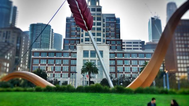 Escultura en San Francisco de un arco con una flecha que impacta contra el suelo de un parque.