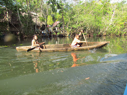 Children rowing dugout canoe on The Rio Dulce