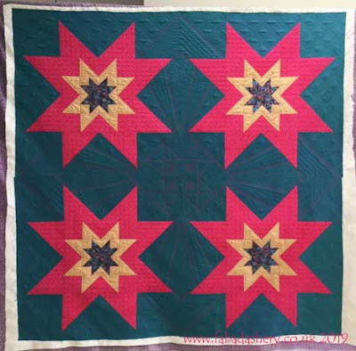 Verna's Eight-Pointed Star quilt in Oakshott Fabrics.  Custom quilted by Frances Meredith, Fabadashry Longarm Quilting