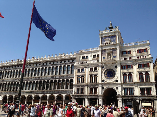 HUge crowds under a European flag on a square with a massive white building