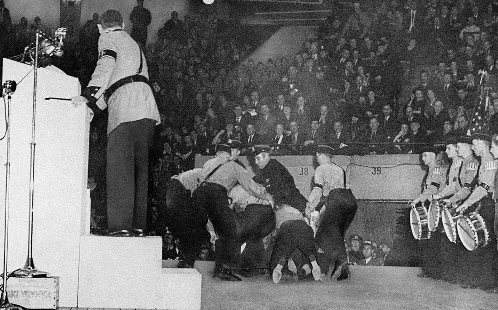 Stormtroopers subdue a heckler on the platform at New York's Madison Square Garden, February 20, 1939. Police who rescued and later arrested the man, whose clothing was torn from him in the struggle, identified him as Isadore Greenbaum, 26, a hotel worker. Fritz Kuhn, National Bund leader, stands on the rostrum, his back turned as he regards the struggle which interrupted his Denunciation of Jews during the Bund rally.