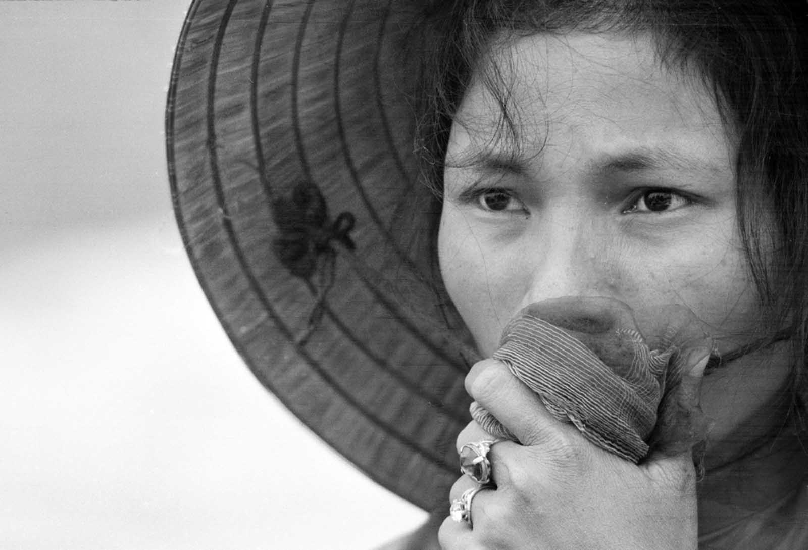 A young South Vietnamese woman covers her mouth as she stares into a mass grave where victims of a reported Viet Cong massacre were being exhumed near Dien Bai village, east of Hue, in April of 1969. The woman's husband, father, and brother had been missing since the Tet Offensive, and were feared to be among those killed by Communist forces.