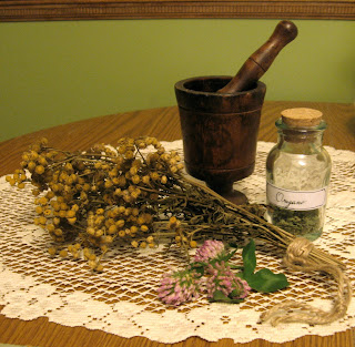 mortar and pestle with dried herbs and bottle of herbs