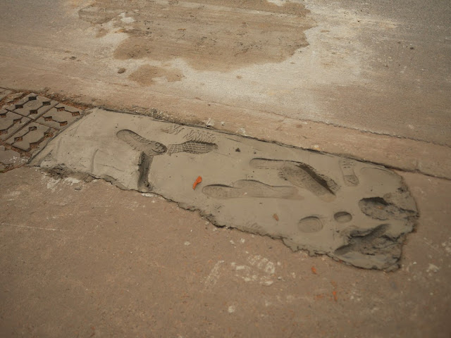 patch of drying concrete with even more footprints