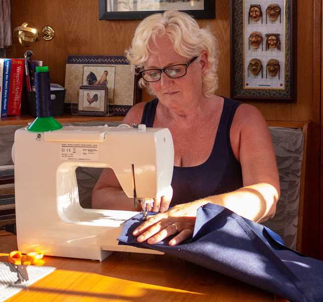 Photo of me using my sewing machine to make a new windlass cover on Ravensdale last summer