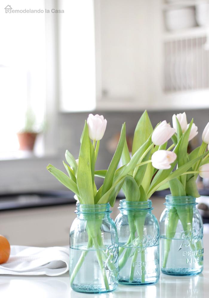 kitchen island decorated with white tulips in blue mason jars - one orange