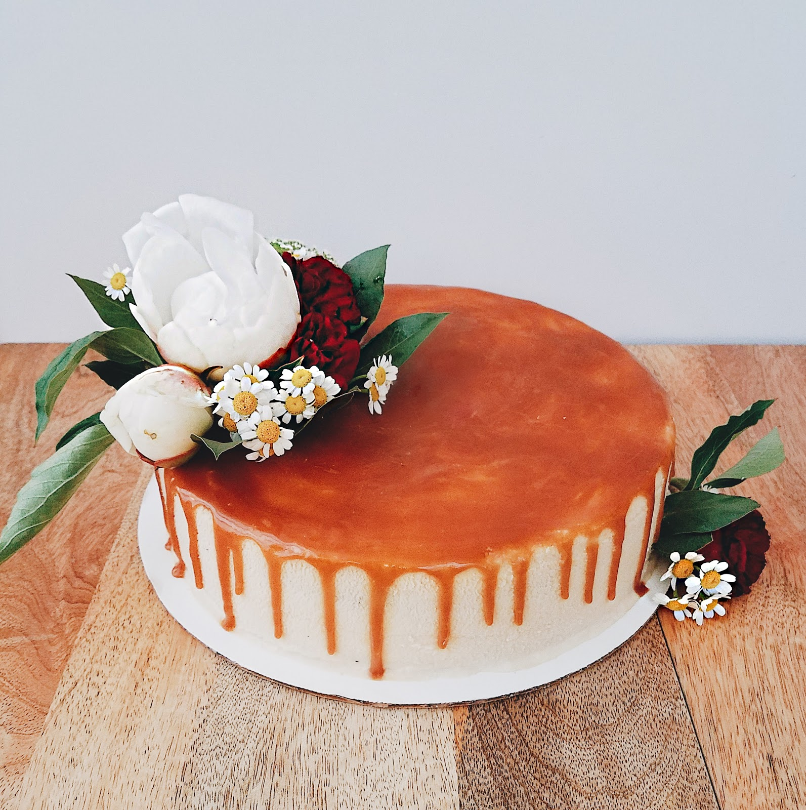 earl grey cheesecake with salty dark caramel topping, decorated with white peonies, red carnations, chamomile flowers, and green mist