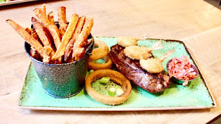 A white rectangular china based plate with a cylindrical matching pot containing dark orange sweet potato fries, a yellow cylindrical corn on the cob, circular light brown onion rings, a dark brown rump steak with black grill marks on the top with tjree dark brown crispy c shaped prawns on a wooden stick on top of it, next to, a pile or red and green chooped vegetables on a light brown rectangular table on a bright background.