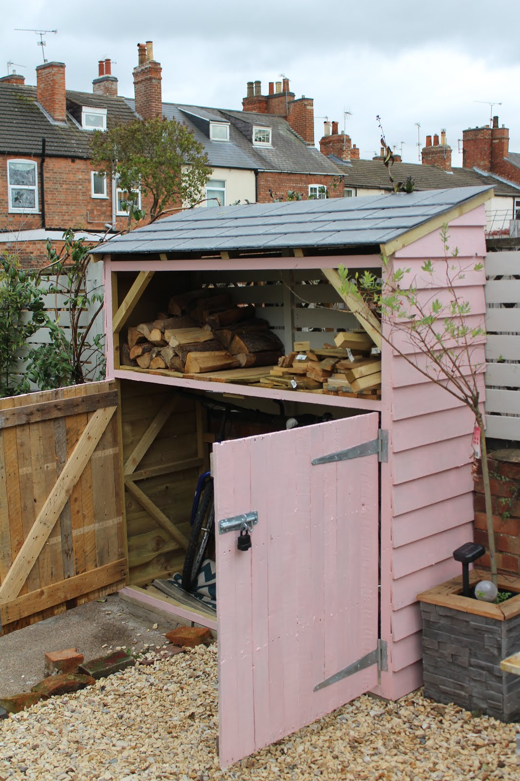 DIY shed with log store at the top