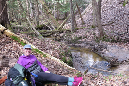 hiker sitting beside a creek