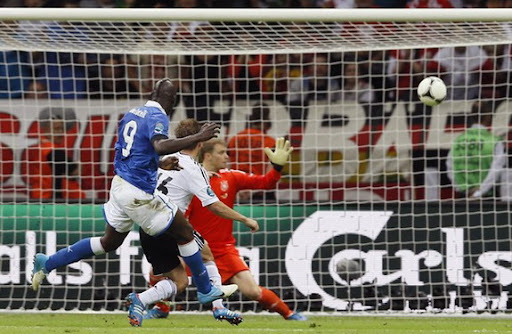 Italian striker Mario Balotelli scores past German goalkeeper Manuel Neuer