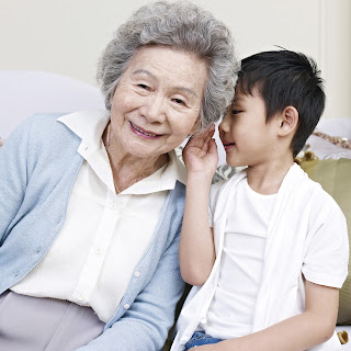 child whispering in an older person's ear