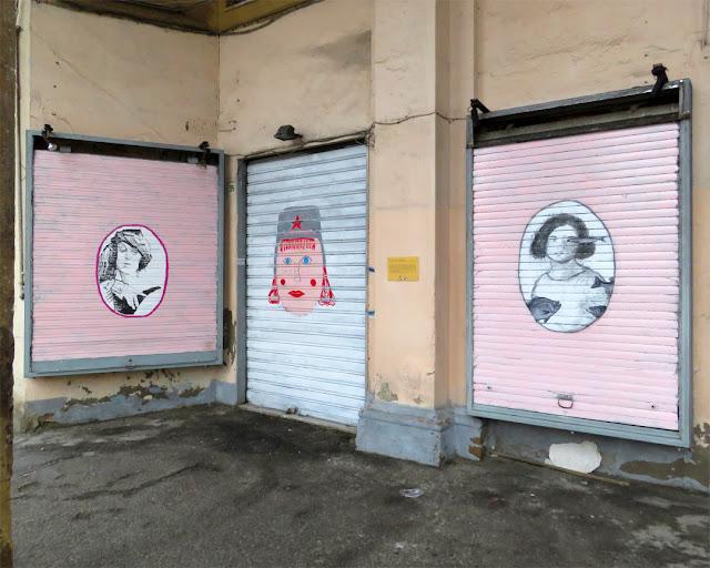 Three decorated shutters under the porticoes of Piazza della Repubblica, Livorno