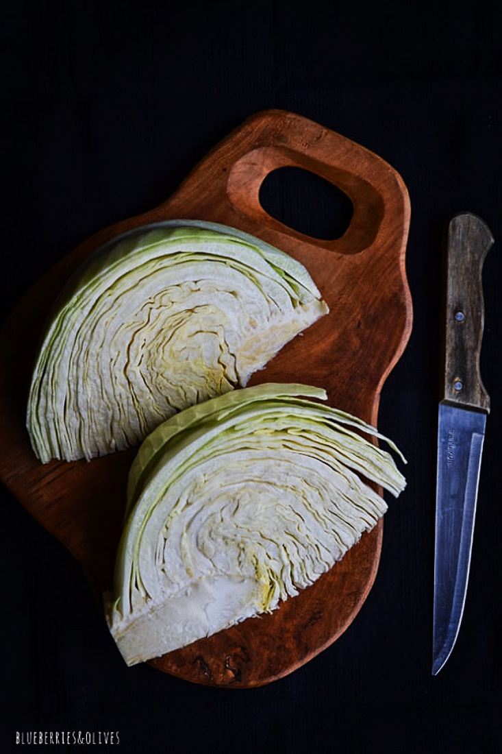 WHITE CABBAGE, WOOD CUTTING BORD WITH KNIFE AND DARK BACKGROUND