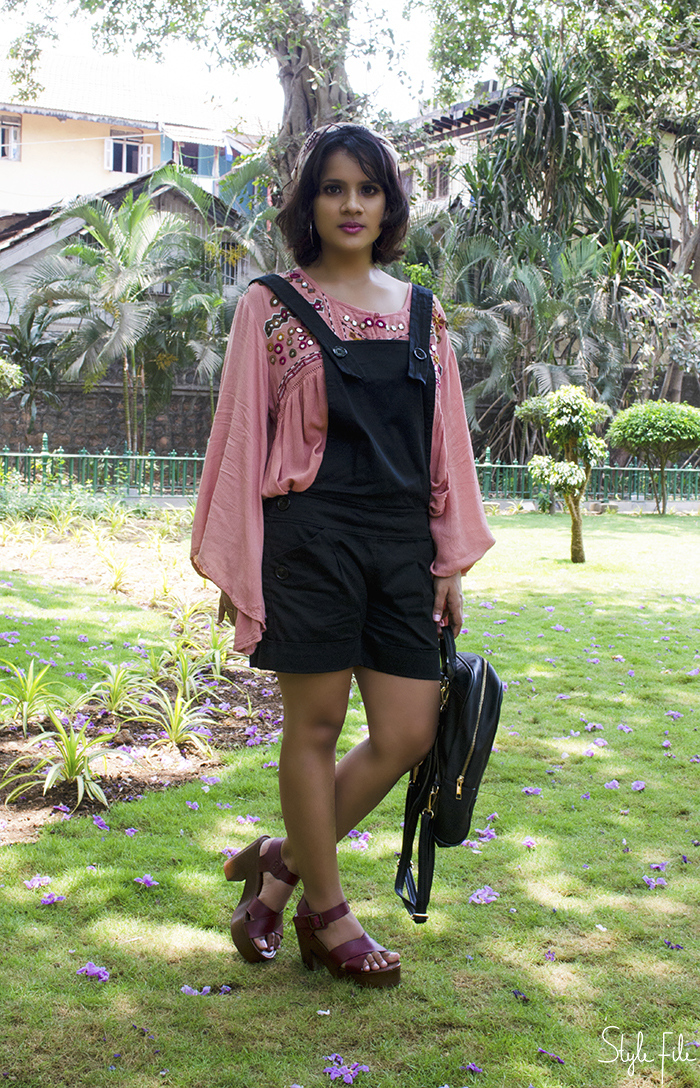 An image of a fashion blogger wearing an outfit of a rose pink blouse with bell sleeves, black dungaree overalls, head scarf, clogs and a pink makeup look